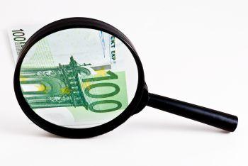 Lupe unter einem 100 Euro Schein