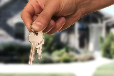Frau mit Schlüsseln vor dem Haus