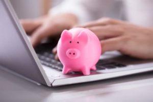 Schweinchen auf Tastatur um Rechtsschutzversicherung Kosten zu sparen